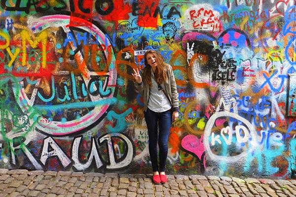 girl in front of graffitied wall